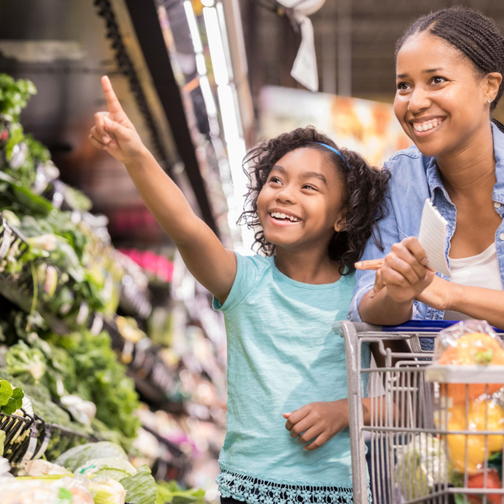Black Women and young Girl in Produce Section Smiling