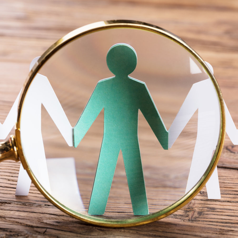 Magnifying Glass on Green Paper Person