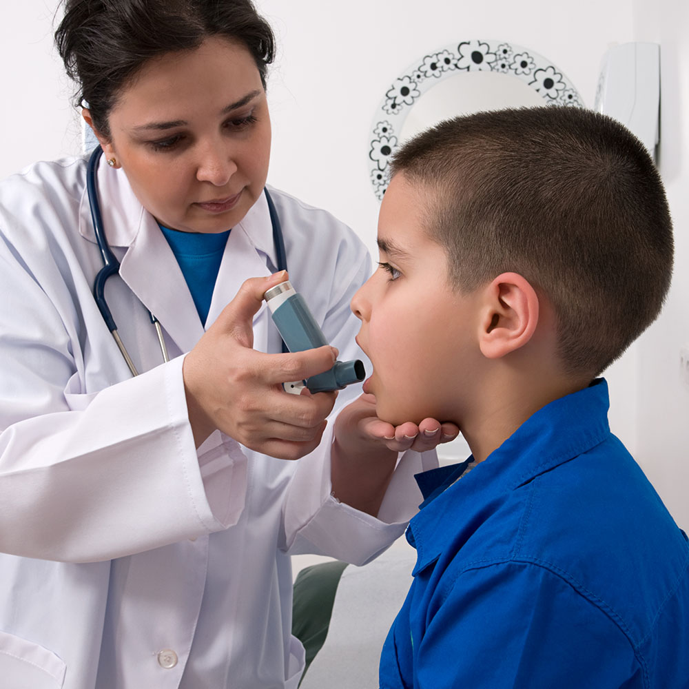 Doctor Administering Asthma Pump to Young Boy